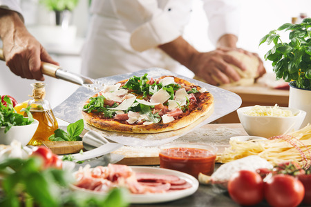 Pizza held on metal peel in kitchen over table with ingredients, cooks hands visible in background, preparing the dough Stock Photo
