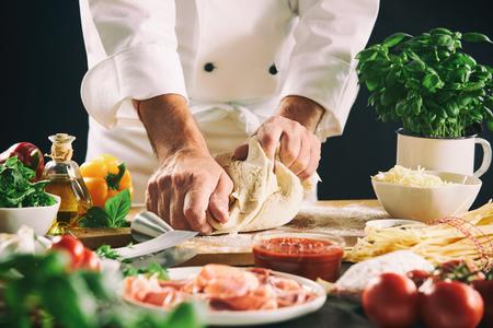 Chef pétrissant la pâte à pâtisserie pour les pâtes ou la pizza dans une vue rapprochée de ses mains et d'un assortiment d'ingrédients frais