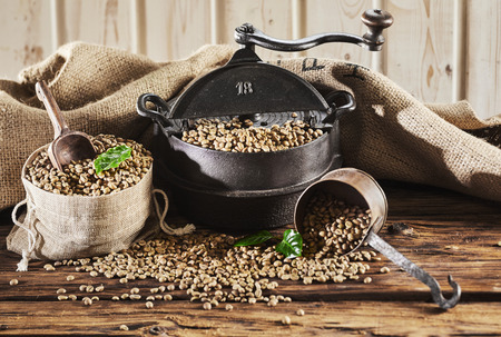 Rustic vintage coffee still life with roaster and raw unroasted coffee beans on an old table with hessian sack background