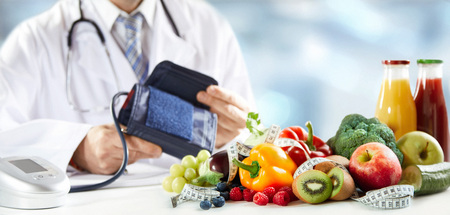 Concepto de dieta saludable y presión arterial con una variedad de coloridas frutas frescas, verduras y batidos frente a las manos de un médico que sostiene un esfigmomanómetro o un manguito en una pancarta panorámica