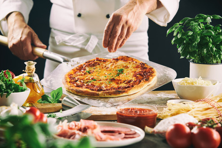 Chef preparing Italian pizza using a paddle with assorted fresh ingredients and herbs in the foreground