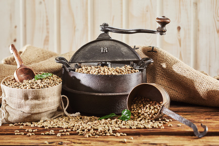 Raw coffee bean still life with vintage cast iron roaster and burlap sack filled with beans and scoop spilling onto a rustic wooden table