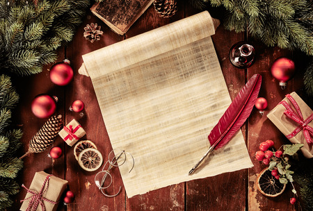 Vintage Christmas still life with scroll and red feather quill surrounded by wrapped gifts, decorations, old reading glasses and pine boughs viewed from above in a festive still lay Stock Photo