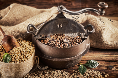 Ancient old cast iron coffee roaster with raw white beans spilling from a rustic hessian sack onto a wooden table