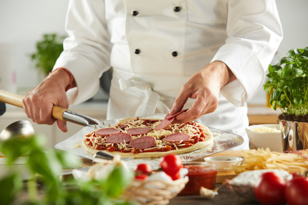 Chef carefully placing round pepperoni slices on pizza next to cutting board covered with grated cheese