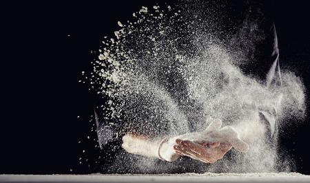 White powdery flour spraying into air while man in black suit wipes his hands over light colored table. Stock Photo