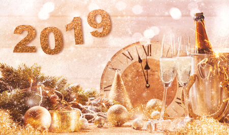 Golden 2019 New Years Eve party background with a clock counting down to midnight and flutes and a bottle of ice cold champagne with scattered decorations and sparkling background bokeh Stock Photo