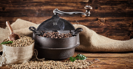 Old vintage cast iron coffee roaster and raw beans in burlap sacks spilling onto a rustic wooden counter in a coffee house in a panorama banner 免版税图像