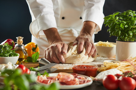 Chef kneading a mound of raw dough for Italian cuisine surrounded by assorted fresh ingredients in a close up on his hands