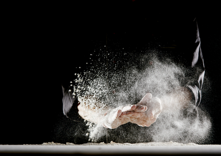 De la farine poudreuse s'envolant dans l'air alors qu'un homme en tenue de chef noir s'essuie les mains sur une table blanche recouverte de farine Banque d'images
