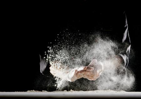 Poedermeel vliegt de lucht in terwijl man in zwarte chef-kokoutfit zijn handen afveegt over witte tafel bedekt met meel Stockfoto
