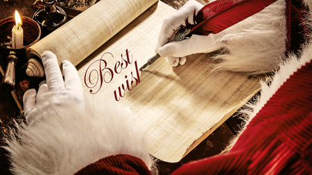 Santa writing a Christmas greeting - Best Wishes - on an old textured vintage parchment scroll with a feather pen in decorative calligraphy in a close up on his gloved hands 写真素材