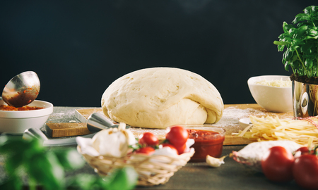 Mound of dough or pastry rising on a floured board surrounded by fresh cooking ingredients against a dark background