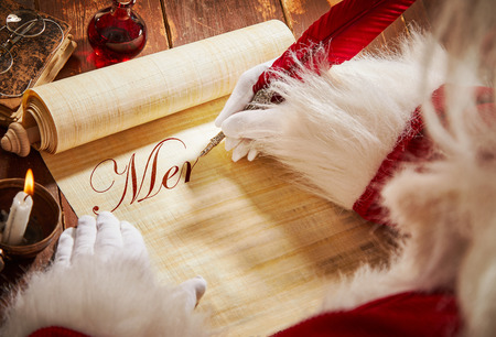 Santa Claus handwriting a Christmas greeting on an old parchment scroll with a feather quill pen on a rustic table in a close up over the shoulder view of his hands