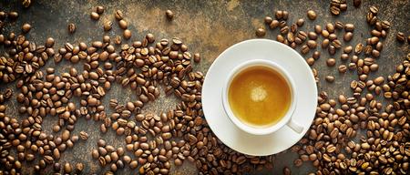 Pancarta panorámica con granos de café tostados y una taza blanca genérica y un platillo de café con leche con leche sobre un fondo de pizarra con textura visto desde arriba Foto de archivo