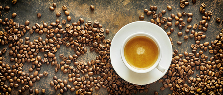 Panorama banner with roasted coffee beans and a generic white cup and saucer of milky latte coffee on a textured slate background viewed from above 스톡 콘텐츠