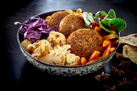 Close-up on bowl of various vegetables and cutlets, viewed from the side on dark table surface