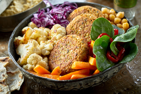 Cutlets and sliced vegetables - carrot, broccoli, chickpea and green leaves served in ceramic bowl. Viewed in closeup from high angle