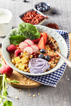 Bawl of muesli with fresh berries and greens, served on rustic wooden chopping board as a healthy breakfast concept