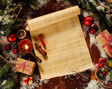 Blank Christmas scroll surrounded by fresh pine foliage and with decorations, winter snow and wax seal in a flat lay still life Stock Photo