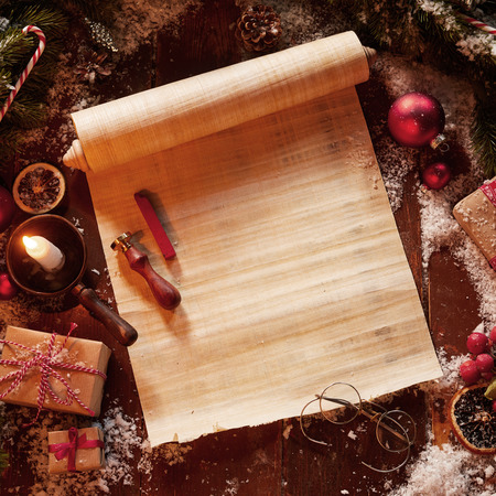 Christmas vintage scroll with spectacles, gifts and decorations surrounded by pine foliage and a burning candle Stock Photo