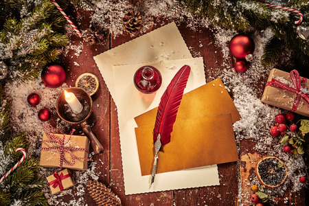 Christmas card background with letter, envelopes and vintage red feather quill pen surrounded by gifts, pine and baubles lit by a burning candle