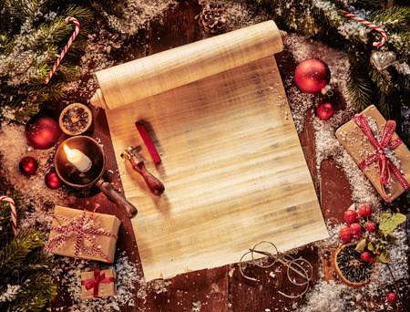Parchment scroll with Christmas decorations and olden day circular reading glasses lit by candlelight with copy space on the paper for your holiday greeting Stock Photo