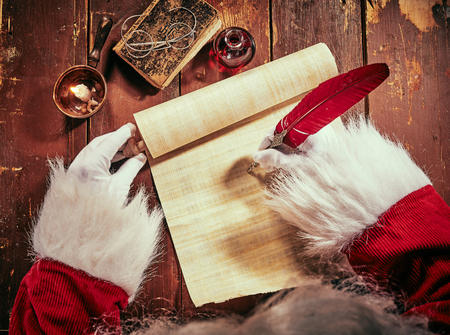 Hands of Santa Claus writing a Christmas letter on a vintage scroll with a red quill pen by candlelight on an old rustic wooden table