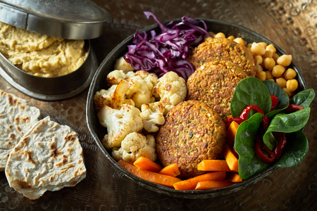 Ceramic bowl of vegetables and cutlets served for eating and shot in close-up from high angle