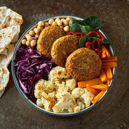 Top view of dish with cutlets and vegetables - cabbage, carrot, chickpeas, and greens