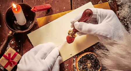 Santa Claus sealing an envelope with a decorative red wax seal showing his face in a close up of his hands lit by candlelight
