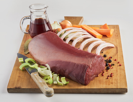 Piece of raw meat and vegetables on wooden board, with knife and small glass jug with red sauce, viewed in closeup from high angle 版權商用圖片 - 112351886