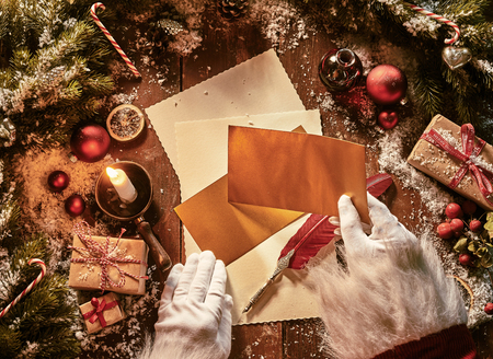 Father Christmas writing a letter to celebrate Xmas in an overhead view of his hands holding envelopes above vintage paper and a feather quill pen surrounded by decorations and gift lit by candlelight