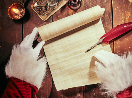 Gloved hands of Father Christmas writing on a vintage parchment scroll with a feather quill pen by candlelight with copy space on the paper