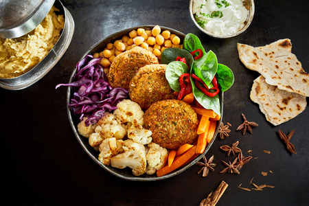 Bowl of meal of vegetables and cutlets, viewed from above on dark table. Decorated and served with bread and sour cream Stock Photo