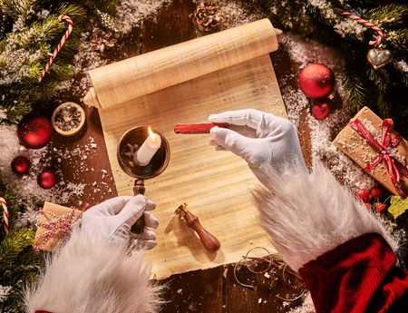 Father Christmas heating sealing wax on a candle flame above an old vintage scroll surrounded by Xmas decorations and gifts in an overhead view
