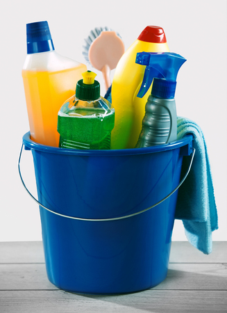 Blue bucket of detergent and chemical cleaner next to brush and cleaning rag sitting on top of grey plank surface