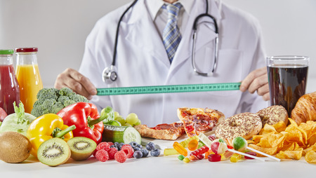 Doctor en abrigo con estetoscopio largo sosteniendo una regla sobre la mesa con una variedad aleatoria de alimentos saludables y no saludables