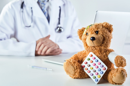 A sick teddy bear with prescription medication from a doctor in a paediatric themed concept.