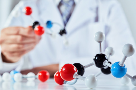 A close up of a scientist in a lab coat demonstrating with molecular structure models.