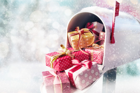 Open white mailbox filled with holiday Christmas presents in decorated boxes and the flag up. New Years and Xmas concept of sending gifts with copy space 免版税图像 - 112788505