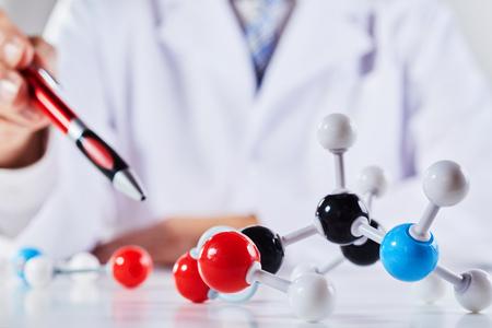 Een close-up van een wetenschapper in een laboratoriumjas die demonstreert met moleculaire structuurmodellen.