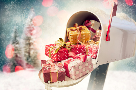 Holiday presents in the open full mailbox with Christmas decorations background. Concept of sending gifts by mail in holiday season with copy space