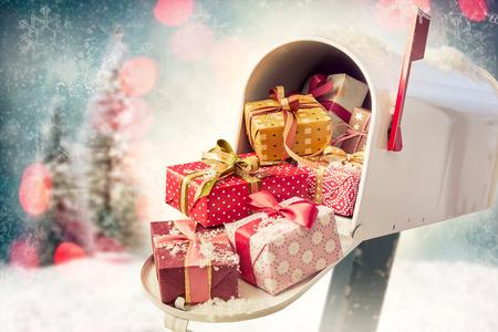 Regalos de vacaciones en el buzón completo abierto con fondo de adornos navideños. Concepto de envío de regalos por correo en temporada navideña con espacio de copia Foto de archivo