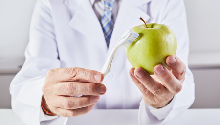 A close up of a scientist in a lab coat cleaning a green apple with a toothbrush.