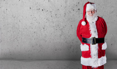 Happy jovial Santa Claus with copy space over a grey textured wall background to wish you a Merry Christmas Imagens