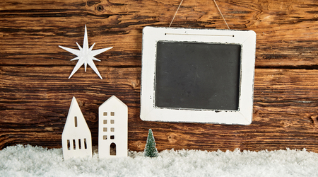 Creative rustic Christmas background with copy space on a vintage wooden school slate with houses and star on a wooden wall with winter snow