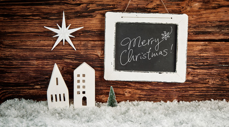 Merry Christmas greeting on a vintage slate with an artistic cutout star over buildings on fresh winter snow against a rustic wooden wall