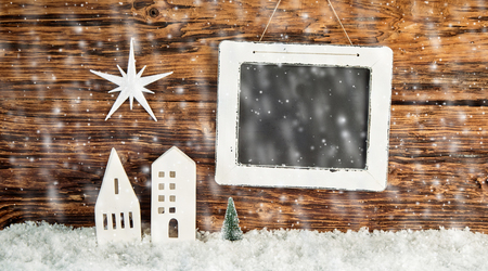 Christmas background with falling winter snow and a star over cutout buildings on a rustic wooden wall with blank vintage slate for your greeting in a panorama banner