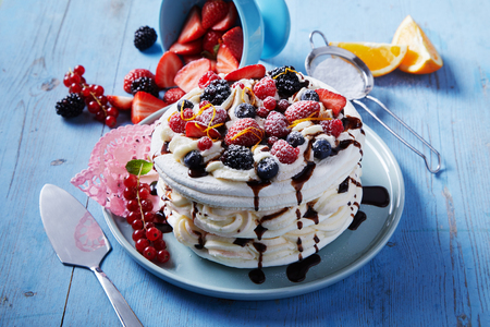 Freshly made Pavlova dessert with layers of meringue and whipped cream topped with an assortment of seasonal berries and orange zest drizzled with chocolate Stock Photo